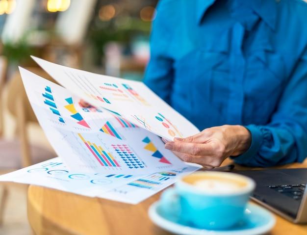 Oudere zakenvrouw omgaan met papier terwijl het hebben van een kopje koffie