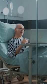 Oudere zieke patiënt die laptop in het bed van de ziekenhuisafdeling gebruikt