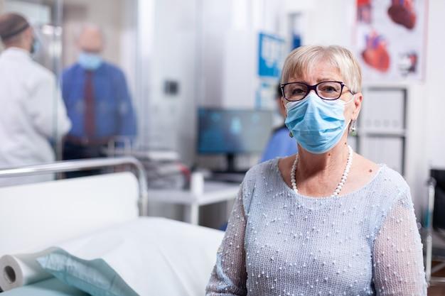 Oudere zieke patiënt met gezichtsmasker in ziekenhuiskast wachtend op dokter