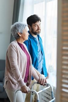 Oudere zoon die voor zijn oudste moeder zorgt die zij bij het raam staan en thuis praten