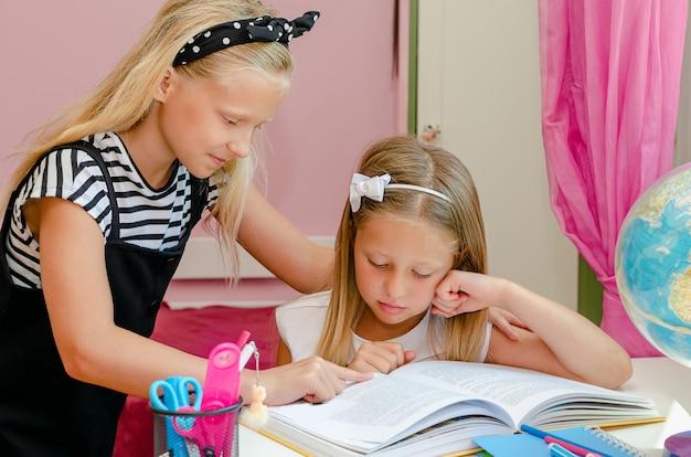Oudere zus helpt haar voorschoolse zus om een boek te lezen. onderwijs concept.