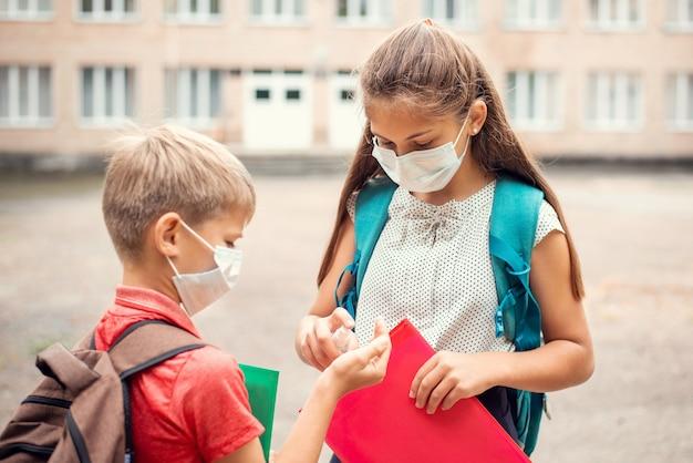 Oudere zus past handdesinfecterend middel toe op haar kleine broertje om handen schoon te maken voor de lessen