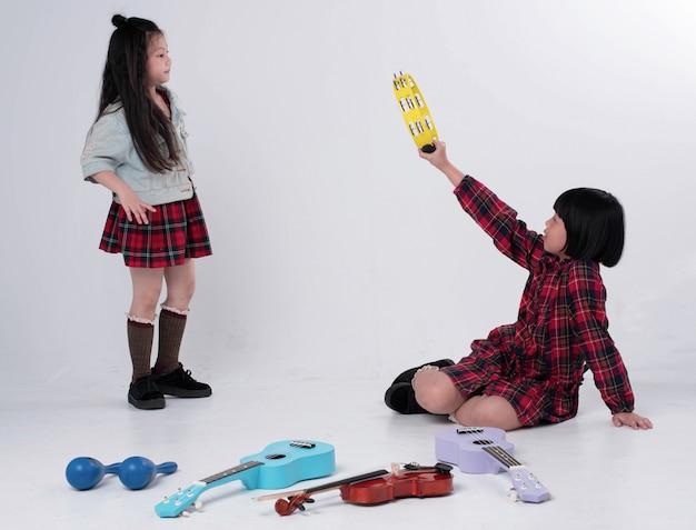 Oudere zus tamboerijn in de hand houden en met jongere zus nemen, samen activiteit doen, gelukkige tijd
