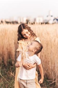 Oudere zus wandelt in de zomer met haar broer in de natuur. gelukkige kinderen broer of zus wandelen en spelen. kinderen spelen buiten