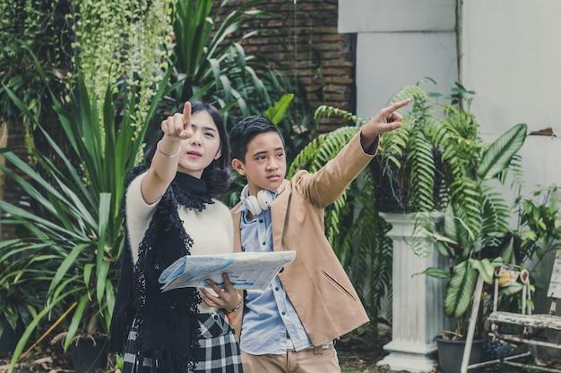 Oudere zuster die de kaart met broer houden wijzend verschilmanier om hotel te vinden