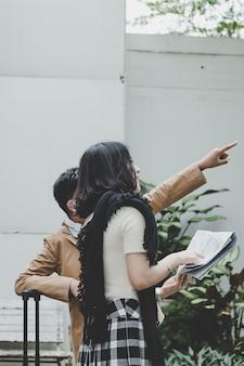 Oudere zuster die de kaart vasthoudt, jonge broer die naar voren wijst. toeristische hotel vinden