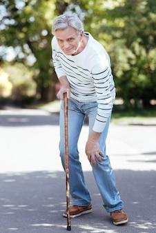 Ouderen betroffen een overstuur man die zijn knie aanraakte en zich slecht voelde terwijl hij leed aan vreselijke pijn in het park