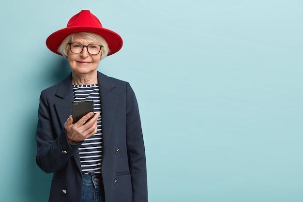 Ouderen en technologieconcept. senior vrouw blijft altijd verbonden, chat via app, stuurt berichten, draagt rode hoofddeksel, gestreepte trui met formele jas, geïsoleerd over blauwe muur