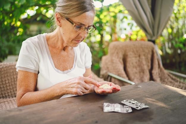 Ouderen gelukkig senior oude vrouw in bril recept bril neemt medicijnen drugs vitaminen pillen buiten in de tuin. gezondheidszorg ouderen levensstijl concept