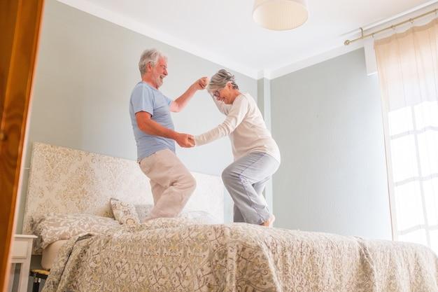 Ouderen gelukkig senior paar hand in hand en dansen samen op bed thuis. zorgeloos actief senior heteroseksueel paar hand in hand en dansen samen op bed thuis
