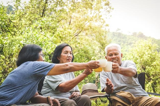 Ouderen groep kamperen in het bos, gelukkig om te ontspannen met pensioen. senior community concepten