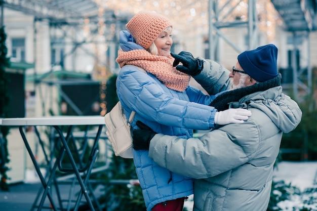 Ouderen in winterkleren ontspannen buiten op een koude dag. vrouw die de linkerschouder van haar man aanraakt