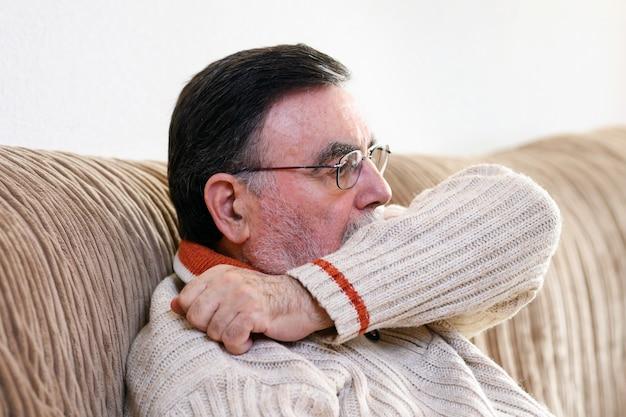 Ouderen niezen, hoesten in haar mouw of elleboog om verspreiding van covid-19 te voorkomen. corona-virus, zieke senior man heeft griep, niezen voor neus, mond met zijn arm.