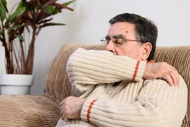 Ouderen niezen, hoesten in haar mouw of elleboog om verspreiding van covid-19 te voorkomen.