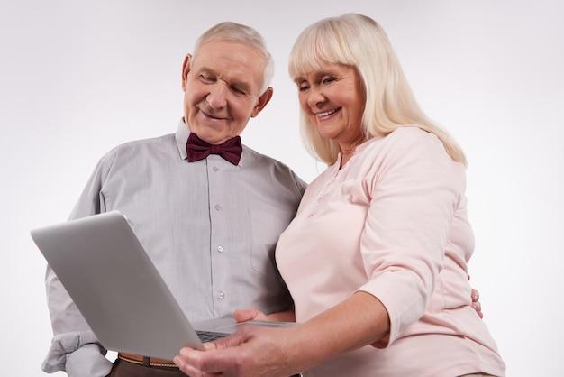 Ouderen paar interactie met laptop.