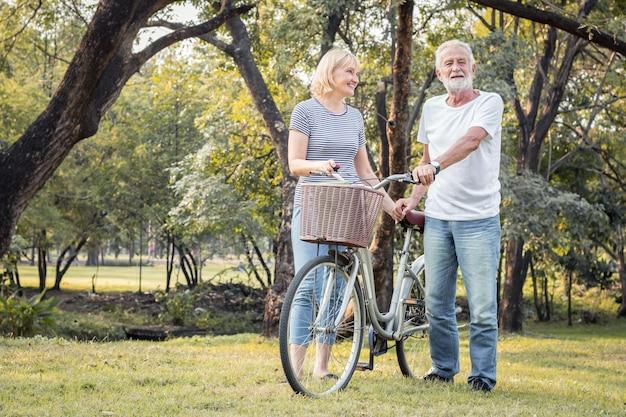 Ouderen paren fietsen samen in het park. oudere stellen spelen samen vrolijk en leuk op de fiets. concept van paren ouderen goed gezond en sterk.