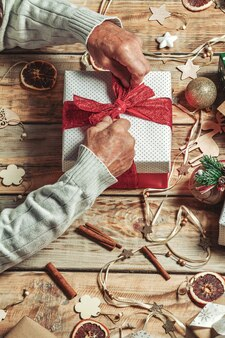 Ouderen senior mans handen kerstcadeaus inpakken