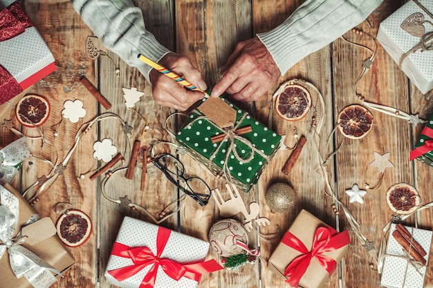 Ouderen senior mans handen ondertekenen kerstcadeaus op tafel met ch