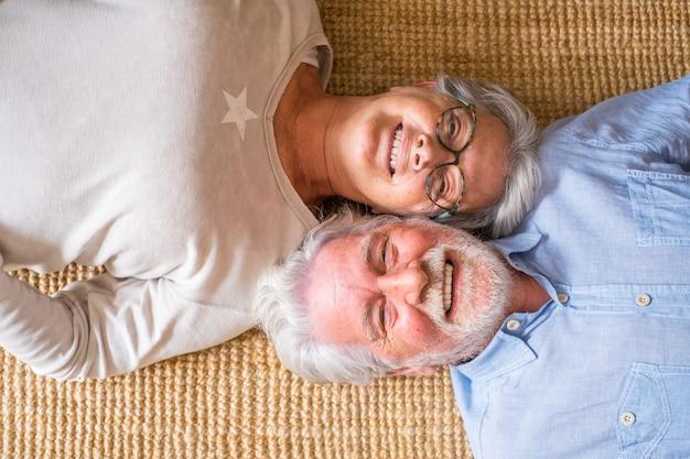 Ouderen senior paar glimlachen terwijl liggend op tapijt in de woonkamer thuis, paar ontspannen op tapijt. bovenaanzicht van gelukkig paar dat thuis op tapijt ligt