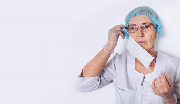 Ouderen triest moe volwassen vrouw arts of verpleegkundige in een witte medische jas, handschoenen, zet op gezichtsmasker het dragen van persoonlijke beschermingsmiddelen geïsoleerd. gezondheidszorg en geneeskunde concept. covid-19-pandemie