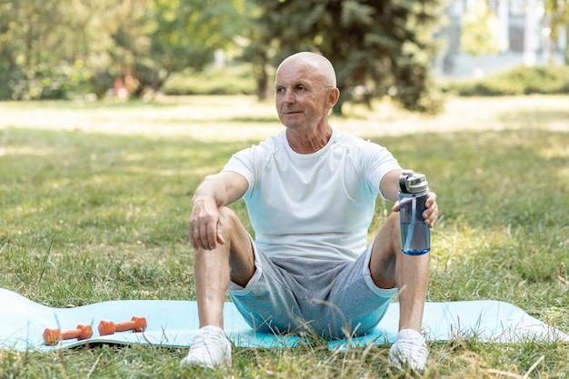 Ouderling die op yogamat in openlucht rust
