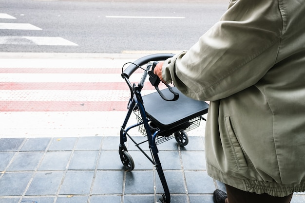 Ouderling die wacht om een zebrapad over te steken, ondersteund door een rollator.