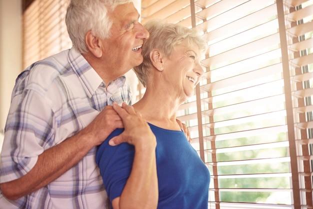 Ouderling huwelijk kijkt door het raam