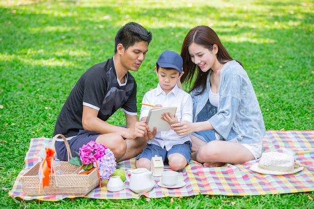 Ouders als lerarenconcept: tienerfamilie met één kind gelukkig onderwijsogenblik in het park.