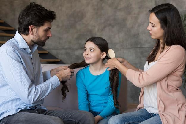 Ouders die dochterhaar borstelen