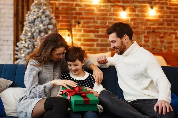 Ouders die geschenkdoos presenteren aan schattige zoon. kerst kinderen, kind, portret. gelukkige familie die kerstochtend samen doorbrengt. wintervakanties, kerstvieringen, nieuwjaarsconcept
