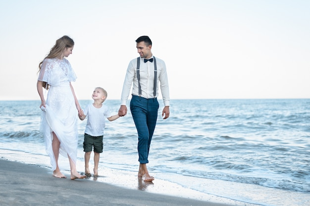 Ouders die handen van zoon houden en op strand lopen. mooi paar met baby op de zee.