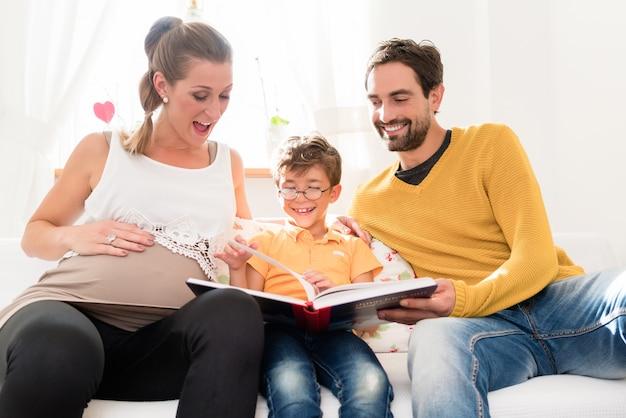 Ouders die hun eerstgeboren zoonfoto's in familiealbum tonen