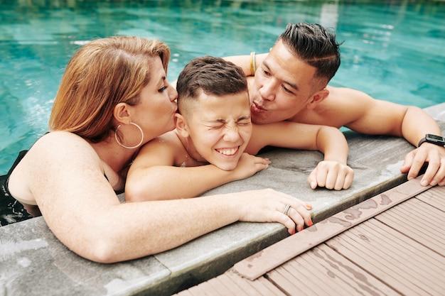 Ouders die hun gelukkig lachende preteen zoon op beide wangen kussen als ze in het zwembad staan
