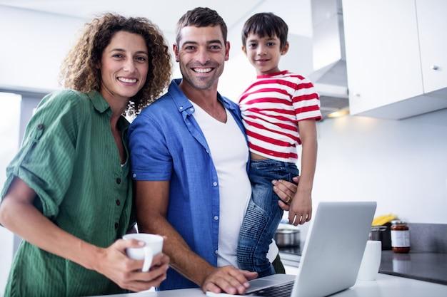 Ouders die laptop met zoon in keuken met behulp van