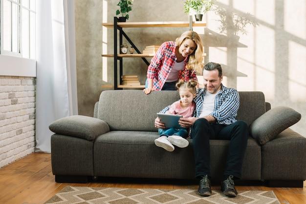 Ouders die met hun jong geitje ontspannen gebruikend digitale tablet in huis