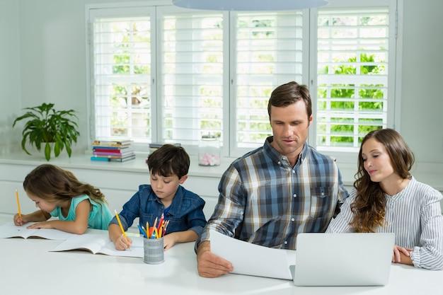 Ouders die met laptop werken en kinderen studeren in de woonkamer