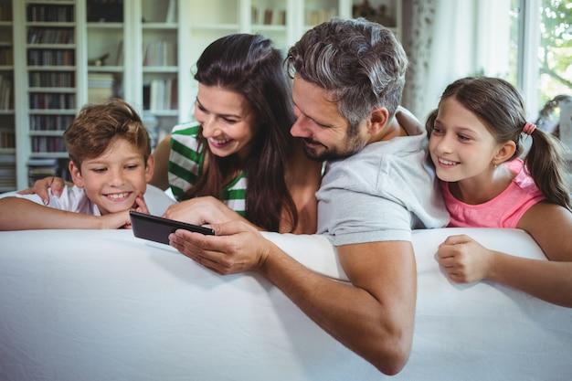 Ouders die op bank met hun kinderen zitten en mobiele telefoon in woonkamer met behulp van