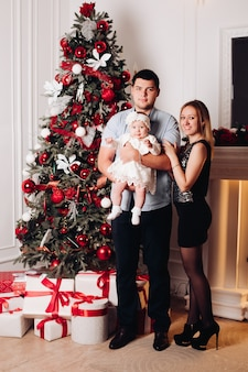 Ouders die op vloer met kind dichtbij kerstmisboom zitten.
