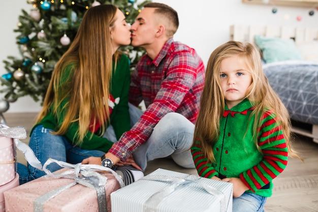 Ouders die voor kerstmisboom kussen