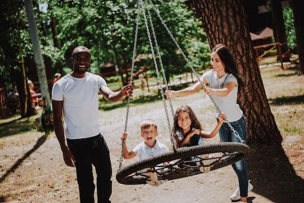 Ouders duwen schommel voor gelukkige kinderen in park.