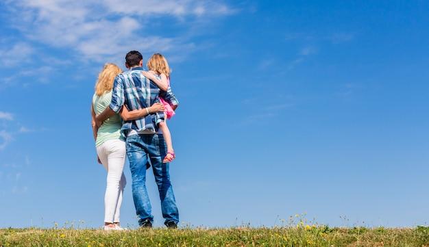 Ouders en dochter, arm in arm in achteraanzicht