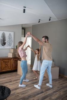 Ouders en dochter dansen en hand in hand