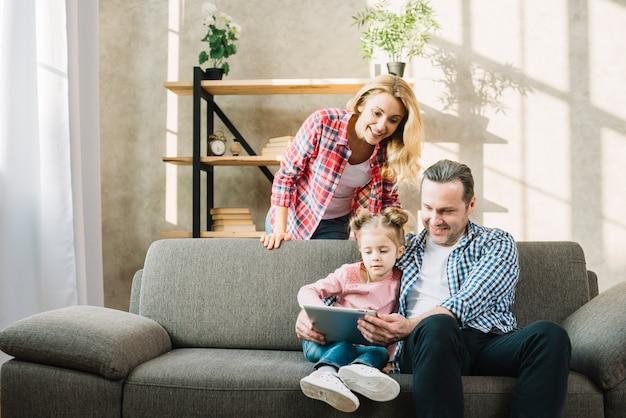 Ouders en dochter die digitale tablet op bank in woonkamer thuis gebruiken