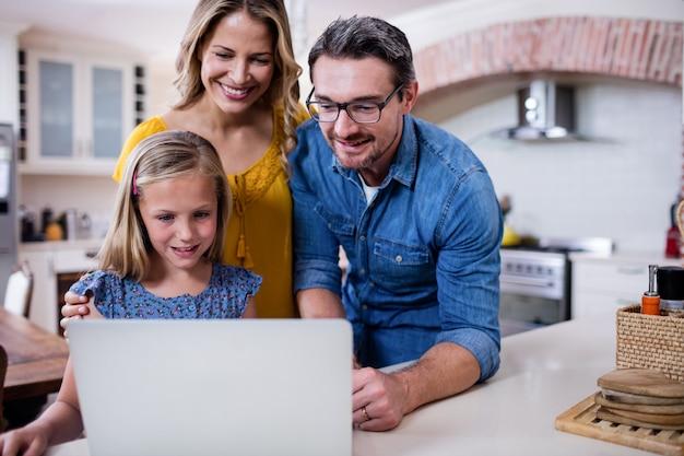 Ouders en dochter die laptop in keuken met behulp van