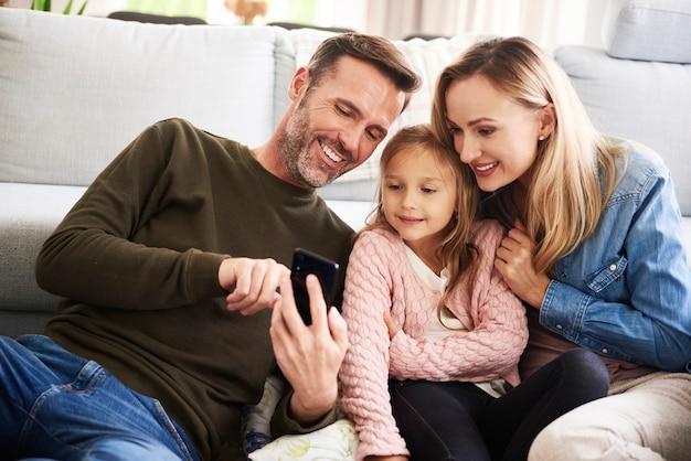 Ouders en hun dochter kijken naar mobiele telefoon