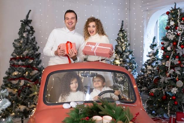 Ouders en hun kinderen met cadeautjes in rode auto in de buurt van kerstbomen.