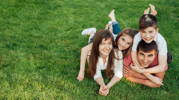 Ouders en hun twee mooie kinderen die op gras in park liggen