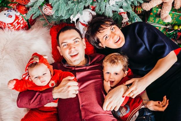 Ouders en hun twee zonen liggen onder de kerstboom