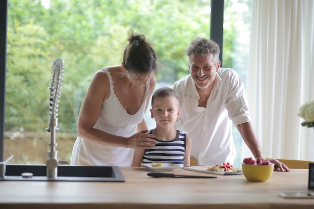Ouders en hun zoon staan tegen het aanrecht met eten erop in het zonlicht