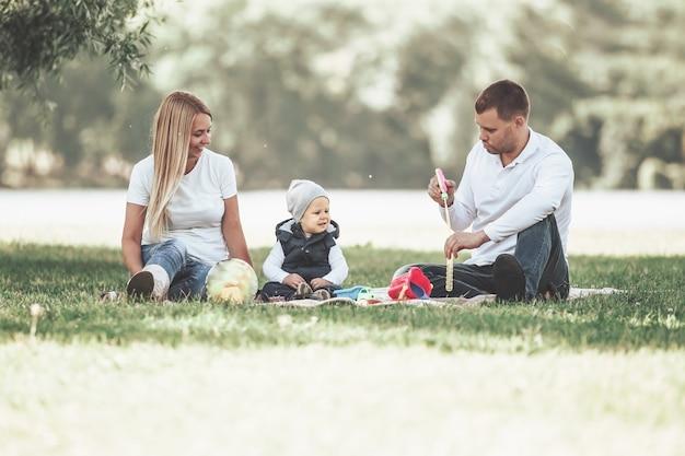 Ouders en hun zoontje bellen blazen op een zomerse dagwandeling. het concept van vaderschap